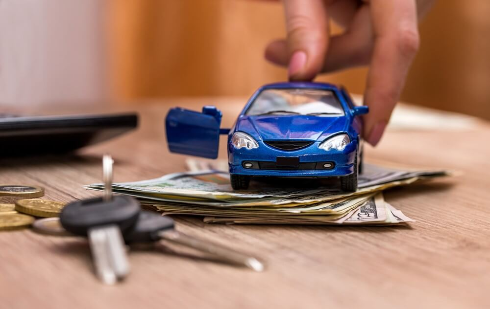 A blue toy car on top of money and sitting besides car keys