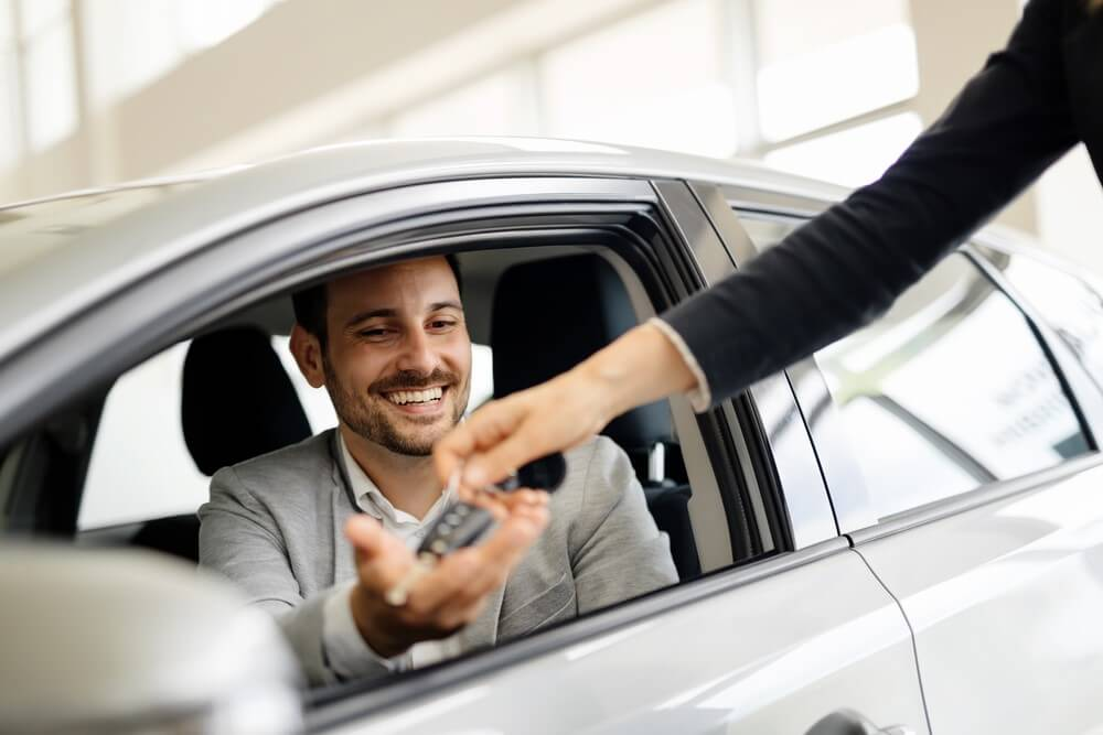 A man receives the keys to the car he purchased from a salesperson.