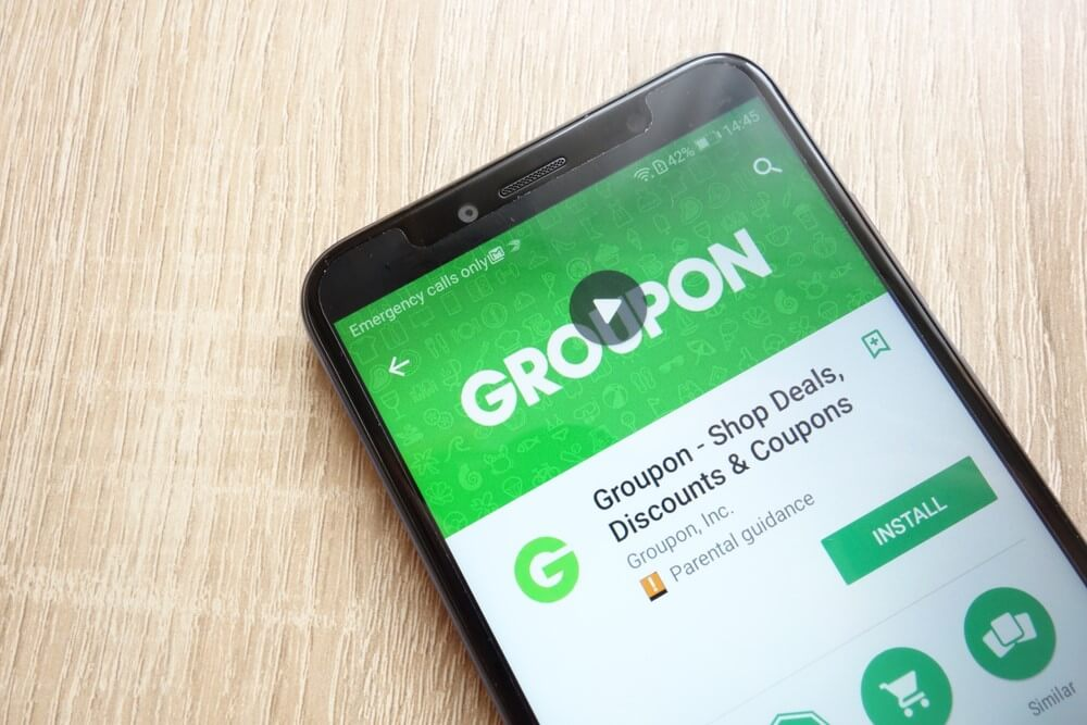 A close up of a smartphone with the Groupon app open.