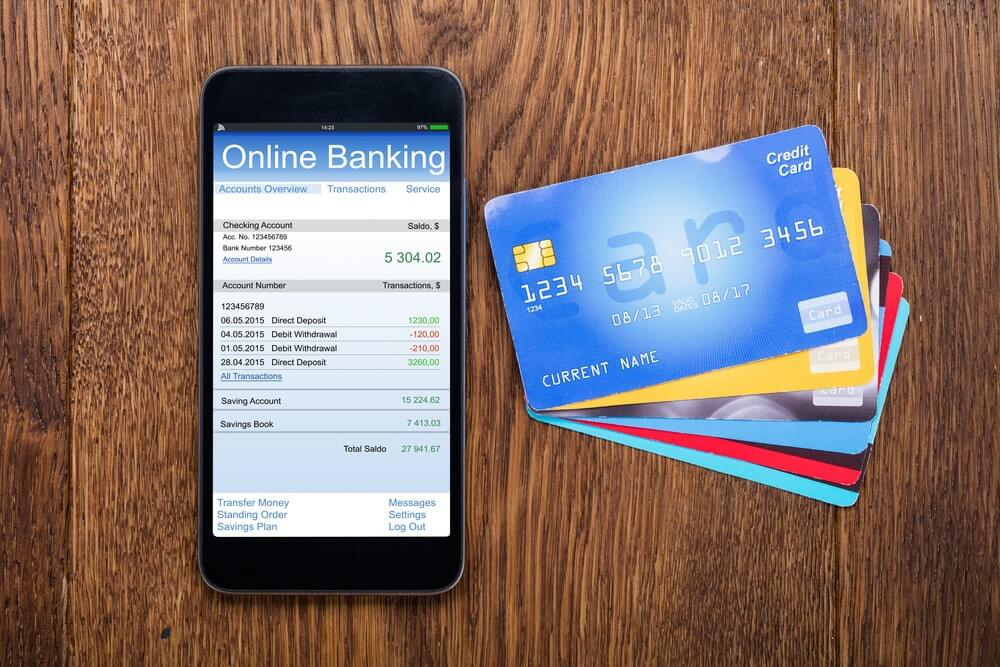 A smart phone displays an online banking site; credit cards rest next to the phone to illustrate financial accounts.