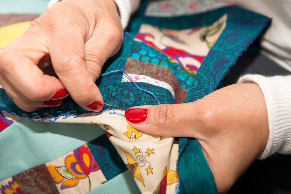 A woman sews a patch on a quilt.