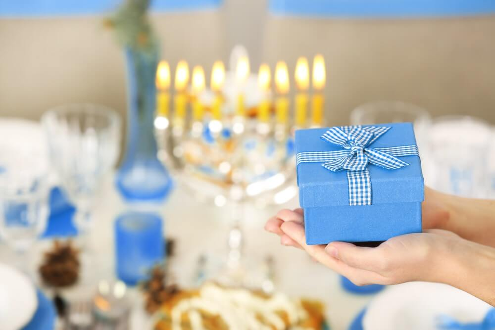 A Hanukkah celebration with a menorah in the background, a woman gives a present wrapped up in blue paper with a white gingham bow.