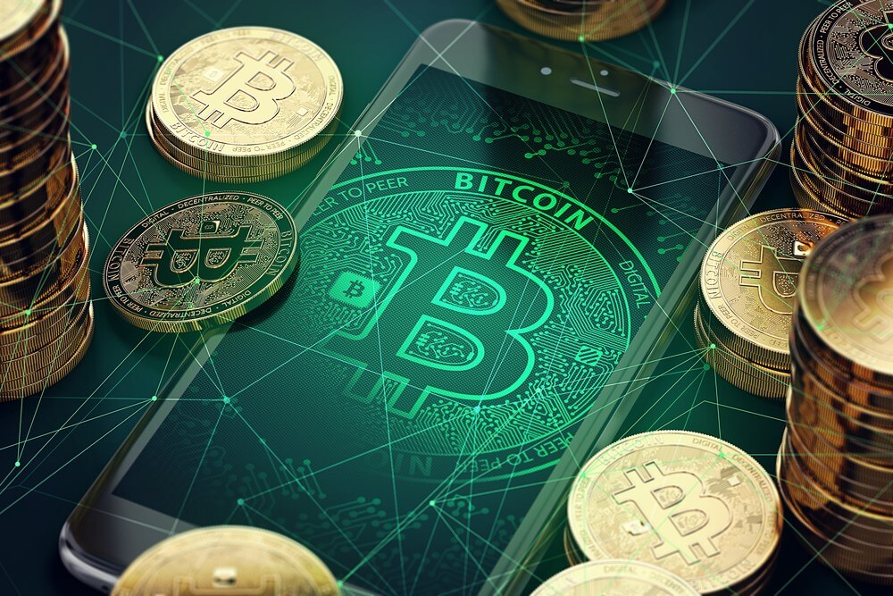 A Bitcoin app is open on a smartphone, with Bitcoins surrounding the device